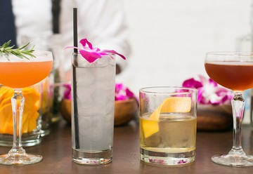 Different Alcoholic Drinks Lined Up On Bar